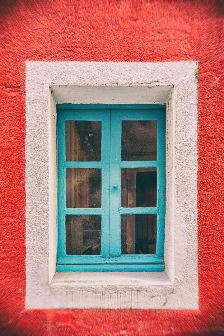 fenêtre bleue avec bords blancs sur mur rouge