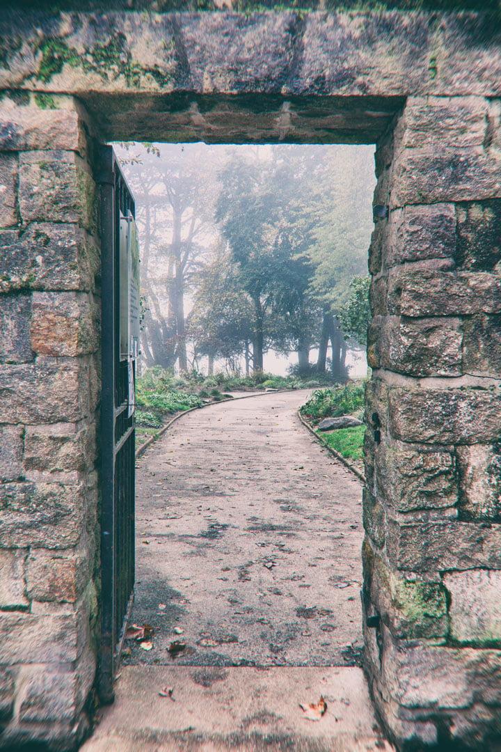 mur en pierre avec porte ouverte vers parc dans la brume