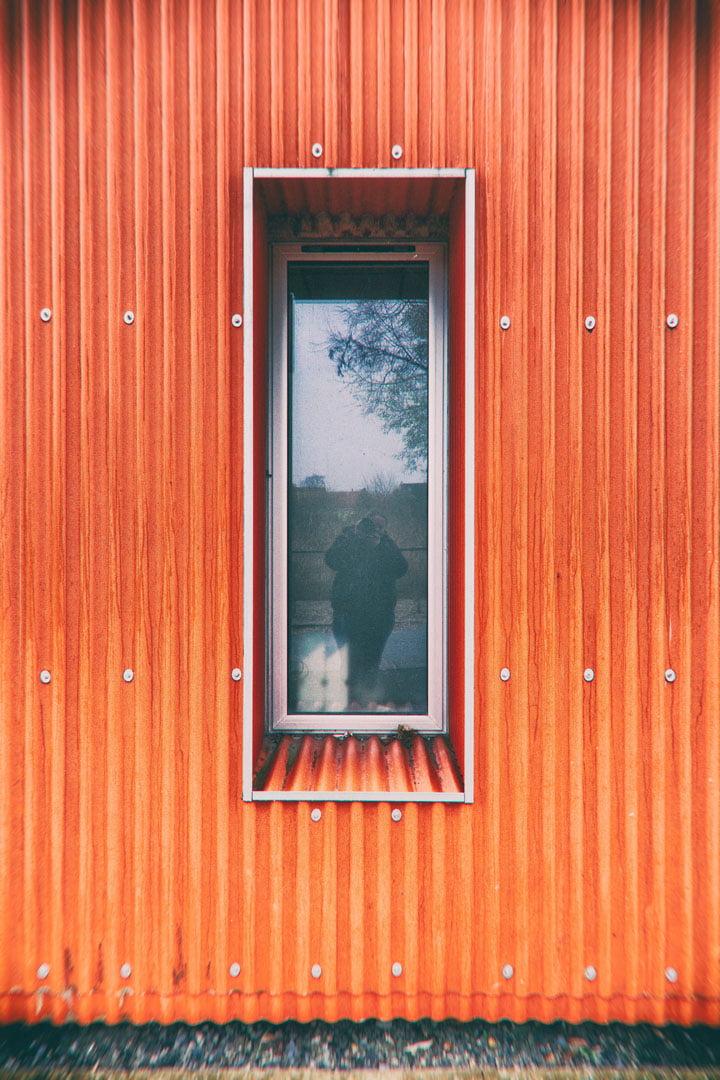autoportrait dans fenêtre entourée de tôle orange