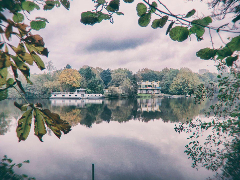 bâtiment et péniche entre les feuilles